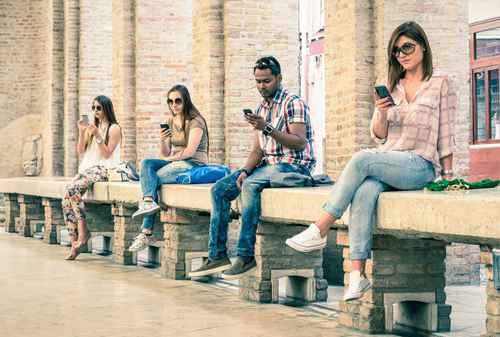 Group of bored multiracial friends using mobile smartphone